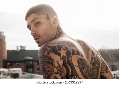 Handsome tattooed man outdoor portrait posing barechested