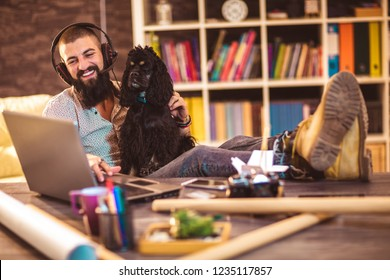 88e26e02f Handsome tattooed man working at home on laptop while sitting at the table  with cute dog