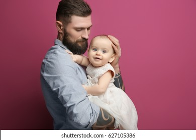 Handsome tattooed young man holding cute little girl on color background