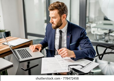 Handsome tax manager dressed in the suit working with documents and laptop at the modern office interior