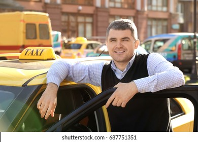 Handsome taxi driver standing near car with opened door on street