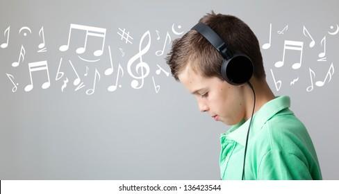 Handsome teen boy listening to music on headphones over grey background