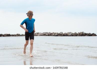 Handsome teen boy running in neoprene swimsuit in Baltic sea