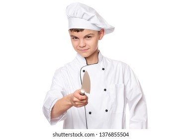 Handsome teen boy wearing chef uniform. Portrait of a cute male child cook with big knife, isolated on white background. Food and cooking concept.
