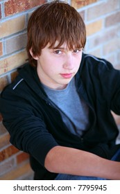 handsome teen guy model seated against brick wall