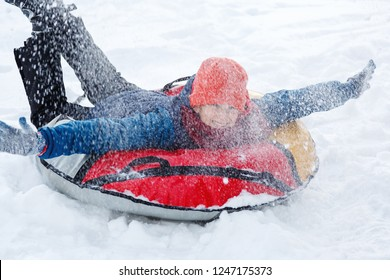 Handsome teen laughing and showing excitement while he slides downhill.  snow tubing on winter day outdoors. Happy cute excited boy sledding downhill on a snowy day. Winter activities