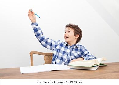 A handsome teenage boy is doing his homework.