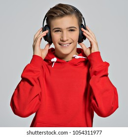 Handsome teenage boy with headphones over head. Young teen listening music on big headphones - posing on white background
