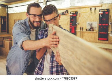 Handsome teenage carpenter and his father in protective glasses are examining wood and smiling while working in the workshop