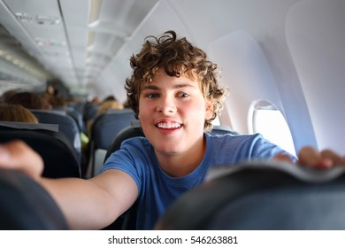 Handsome teenager boy with curly hair smiles in airplane during travel