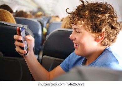 Handsome teenager boy with curly hair holds ohone in airplane during travel