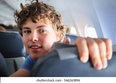 Handsome teenager boy looks into camera in airplane during trip
