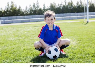 A handsome teenager boy play football outside
