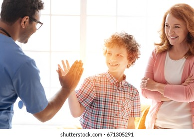 Handsome teenager giving high-five to his friend