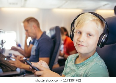 Handsome teenager listening music in airplane and looking at camera. Boy listening music in earphones.