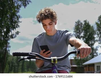 gut aussehende Teenager, die mit dem Fahrrad fahren und Smartphone anschauen. Verwendung von Boten oder sozialen Medien oder SMS. aktive Lebensdauer, Sommeraktivität. neugieriger Junge. Kaukasier auf einem Fahrrad auf dem Land.