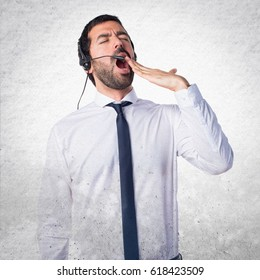 Handsome telemarketer man yawning on textured background