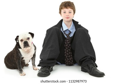 Handsome ten year old american boy in baggy suit sitting against white wall with Bulldog.