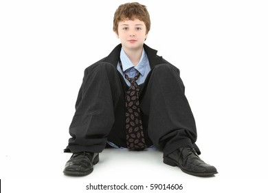 Handsome ten year old american boy in baggy suit sitting against white wall over white.