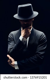 Handsome thoughtful man in black suit and hat touching chin isolated on dark background