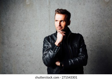 Handsome thoughtful man in leather jacket standing against concrete wall and looking away