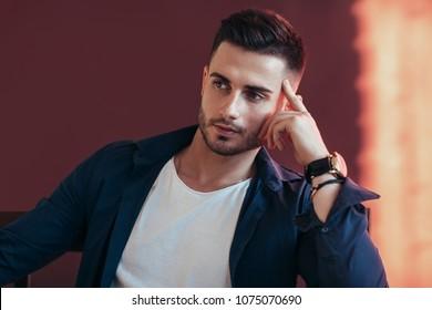 Handsome thoughtful man on dark red background.
