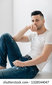 Handsome thoughtful man portrait sitting on floor