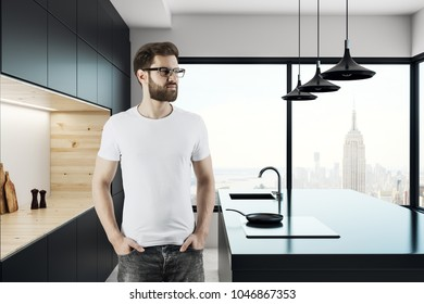 Handsome thoughtful young man standing in creative kitchen interior with panoramic New York city view.