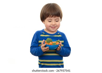 Handsome toddler boy isolated on white background holding blue bowl of fresh vegetables.  Three year old preschooler holding carrots and broccoli, looking down at healthy food, ready to eat nutritious