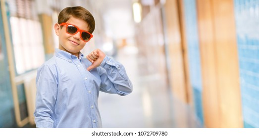 Handsome toddler child with green eyes proud, excited and arrogant, pointing with victory face at school corridor