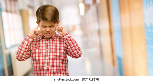 Handsome toddler child with green eyes covering ears ignoring annoying loud noise, plugs ears to avoid hearing sound. Noisy music is a problem. at school corridor