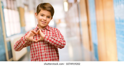 Handsome toddler child with green eyes happy showing love with hands in heart shape expressing healthy and marriage symbol at school corridor