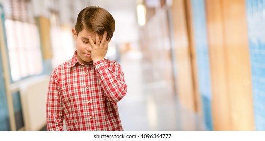 Handsome toddler child with green eyes stressful keeping hand on head, tired and frustrated at school corridor