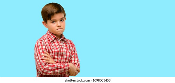 Handsome toddler child with green eyes nervous and scared biting lips looking camera with impatient expression, pensive over blue background