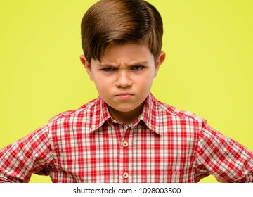 Handsome toddler child with green eyes irritated and angry expressing negative emotion, annoyed with someone over yellow background