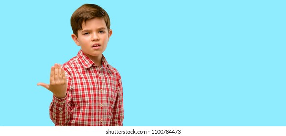 Handsome toddler child with green eyes irritated and angry expressing negative emotion, annoyed with someone over blue background