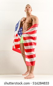 Stock photo naked handsome fitness guy standing against the wall with american flag