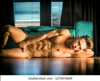 Handsome totally naked muscular young man laying down on hardwood floor at home in seductive attitude, looking at camera