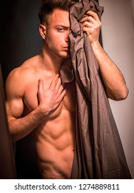 Handsome totally naked muscular young man at home covering nudity with drapes by large windows, in seductive attitude, looking at camera