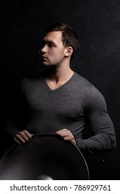 Handsome tough guy on a black background. Holding on to the back of the chair. Portrait. Brawn. Gray sweater. Force. Masculinity.