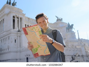 Handsome tourist guy holding a city map looking at the camera and smiling at the beautiful sunny day at the Rome, Italy. The famous Vittorio Emanuele II monument at Piazza Venezia