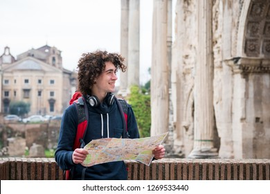 Handsome tourist holding a tourist map near Roman forum in Rome, Italy.