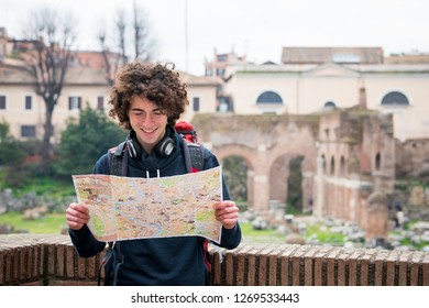 Handsome tourist looking at tourist map near Roman forum in Rome, Italy.