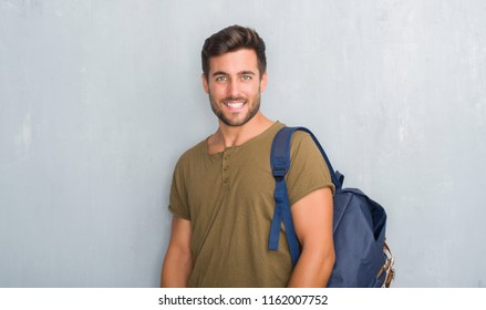 Handsome tourist young man over grey grunge wall wearing backpack with a happy and cool smile on face. Lucky person.