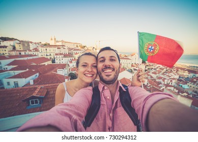 handsome tourists couple take selfie photo with view on Lisbon,Portugal from miradouro on sunny clear day holding portugal flag.Honeymoon loving romantic couple traveling to european city for holiday