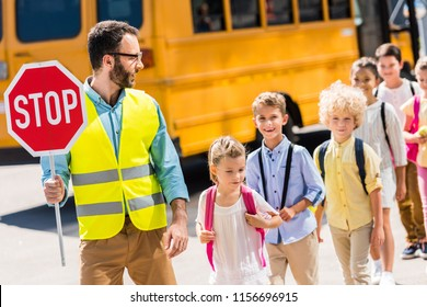 handsome traffic guard crossing road with pupils in front of school bus