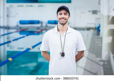 Handsome trainer standing with hands on the back at the pool