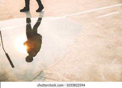 A handsome traveler or backpacker walk on street, reflection his shadow on the water, sunset in summer season. It's hot day. Attractive guy love travel when he get holiday or vacation, copy space