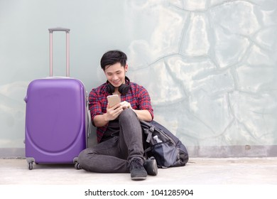 Handsome traveler guy feels happiness because cool man can find the way to go to his destination by using some application for searching the way on his smartphone. A phone get good signal and full bar