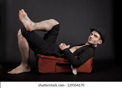 Handsome traveler lying on an orange suitcase barefoot, isolated on black background